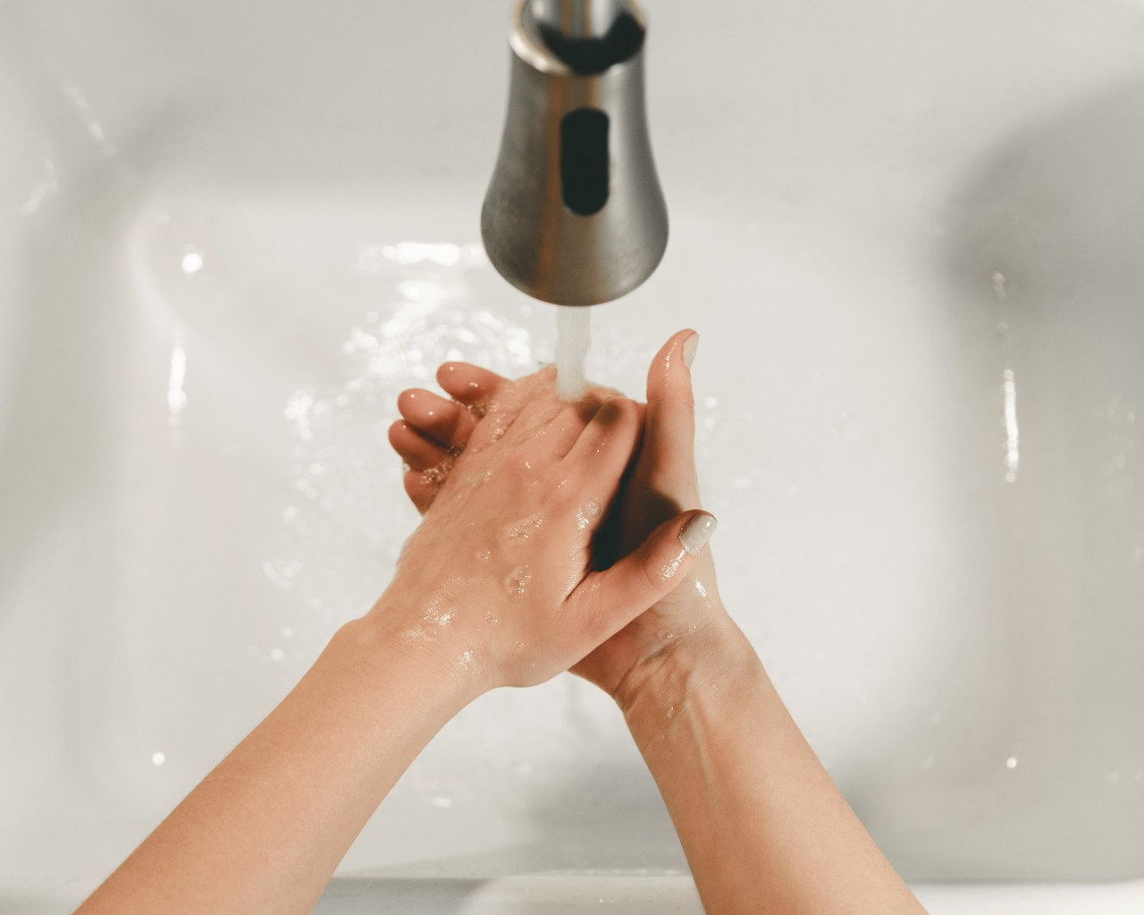 Person washing hands to prevent spread of germs